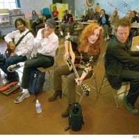 """Tom Waits (far right), Bonnie Raitt, Norton Buffalo, Austin Willacy and Jason Newsted - Bonnie Raitt told the kids at Spring Valley Elementary about learning guitar when she was 8 years old. Her hands weren't large enough to span the fretboard and make an F chord, so she learned to do it with her thumb.  """"Tell Bonnie what we call the F chord,"""" said their guitar teacher, Laura Chinn-Smoot.  """"The ouch chord,"""" a couple of dozen young public school guitar students said in unison.  Raitt inveigled her old pal Tom Waits to join her on piano and sing a duet of """"Sweet and Shiny Eyes,"""" a song they knew from touring together a few years back when Jerry Ford was still president. Former Metallica bassist Jason Newsted, currently playing with Ozzy Osbourne, picked up his bass, and Norton Buffalo added a little harmonica . . . Raitt, Waits, Buffalo jam with S.F. schoolkids - 10/21/2003  ©David Paul Morris"""